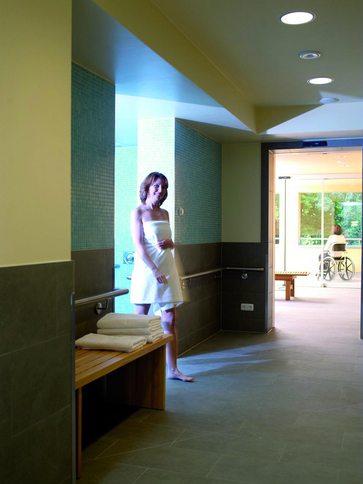 Frau mit Handtuch geht durch die großzügigen Räume des Wellnesssbereichs